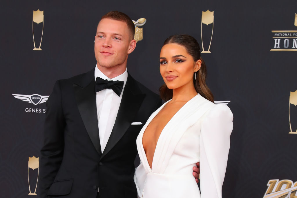 Christian McCaffrey and Olivia Culpo smiling in front of a repeating background