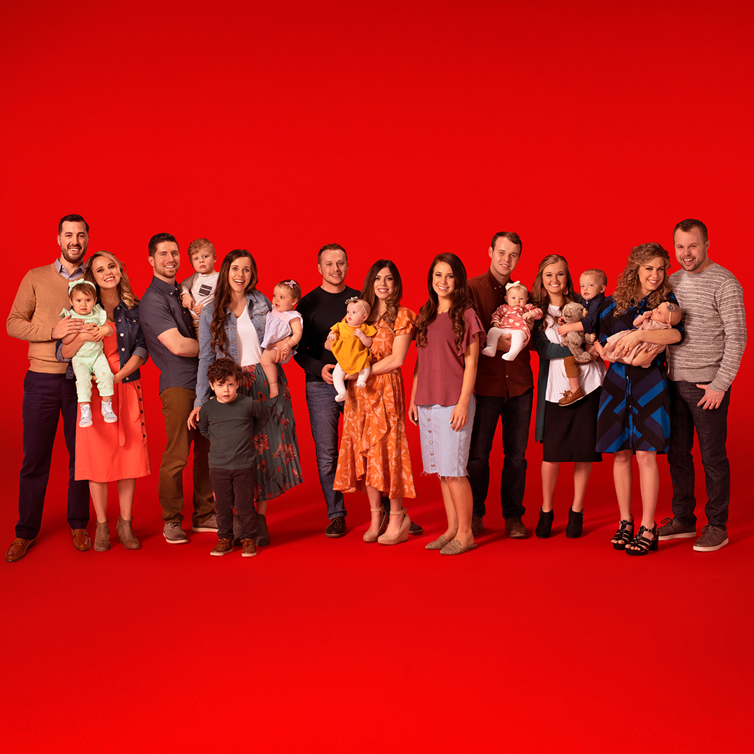 Group photo of Duggar family children and grandchildren on a red background.