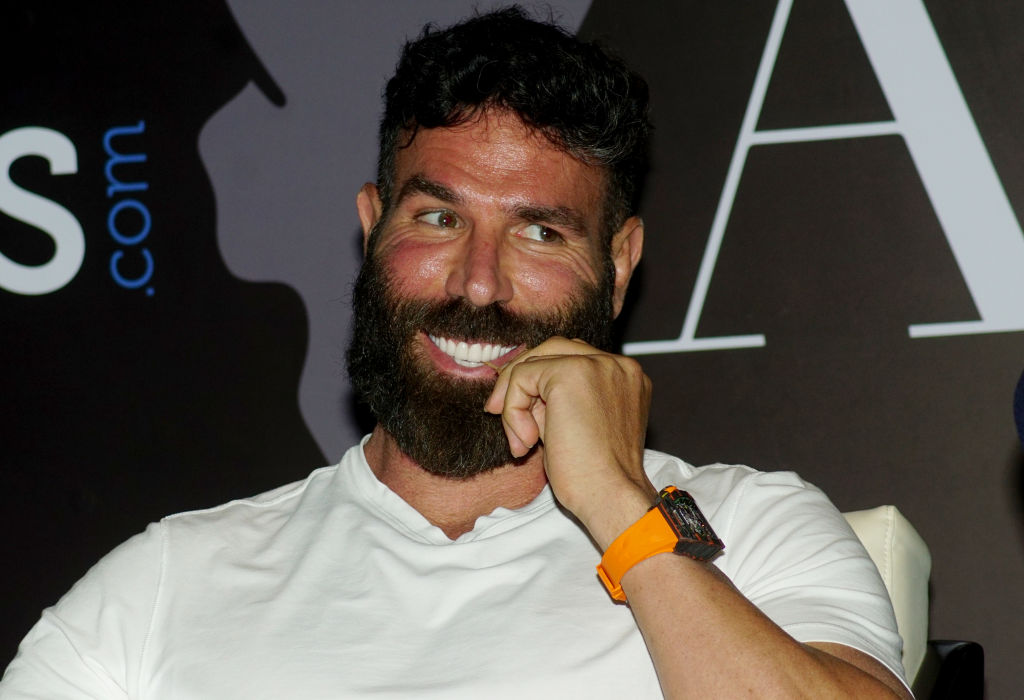 Dan Bilzerian smiling with his hand near his mouth
