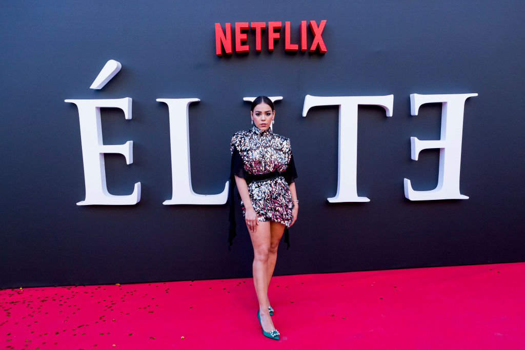 Danna Paola smiling on the red carpet in front of an 'Elite' background