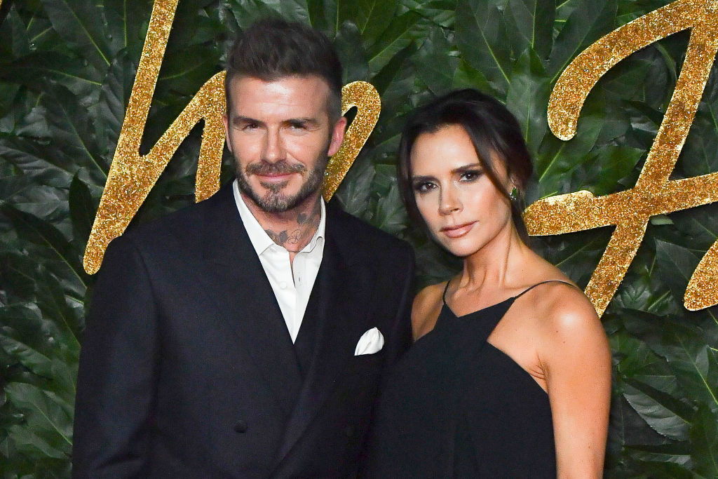 David Beckham and Victoria Beckham smiling in front of a green background