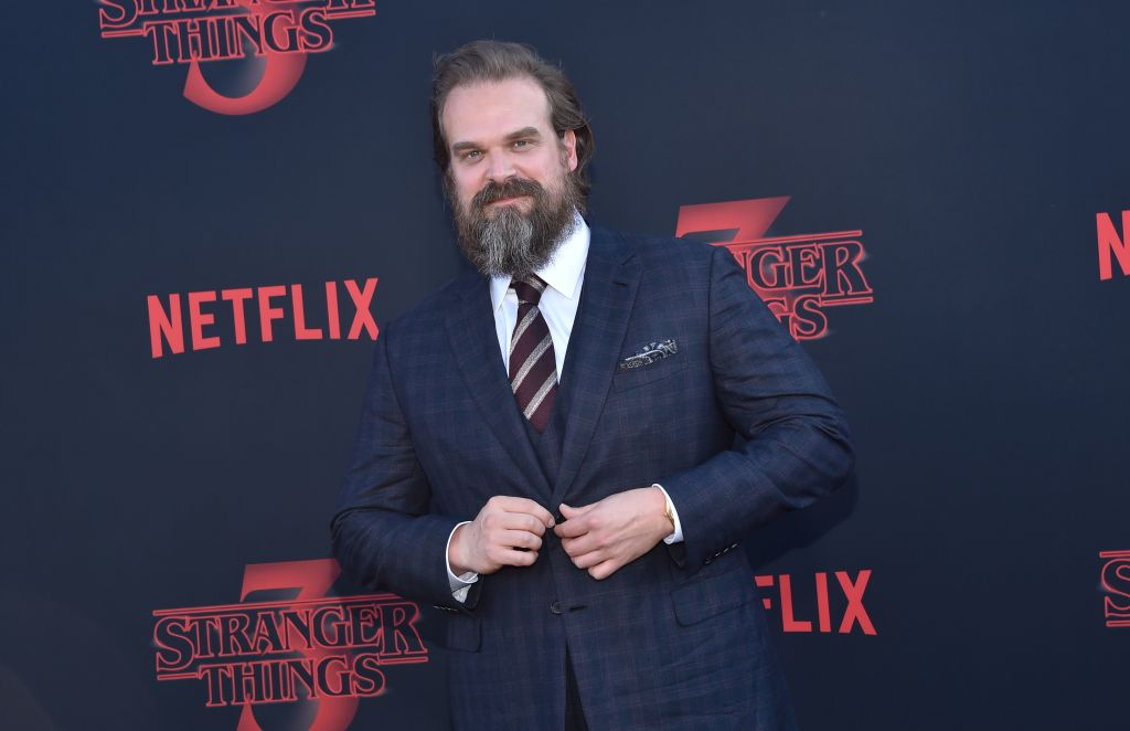 David Harbour buttoning his jacket, smiling, in front of a repeating background with the 'Stranger Things' logo