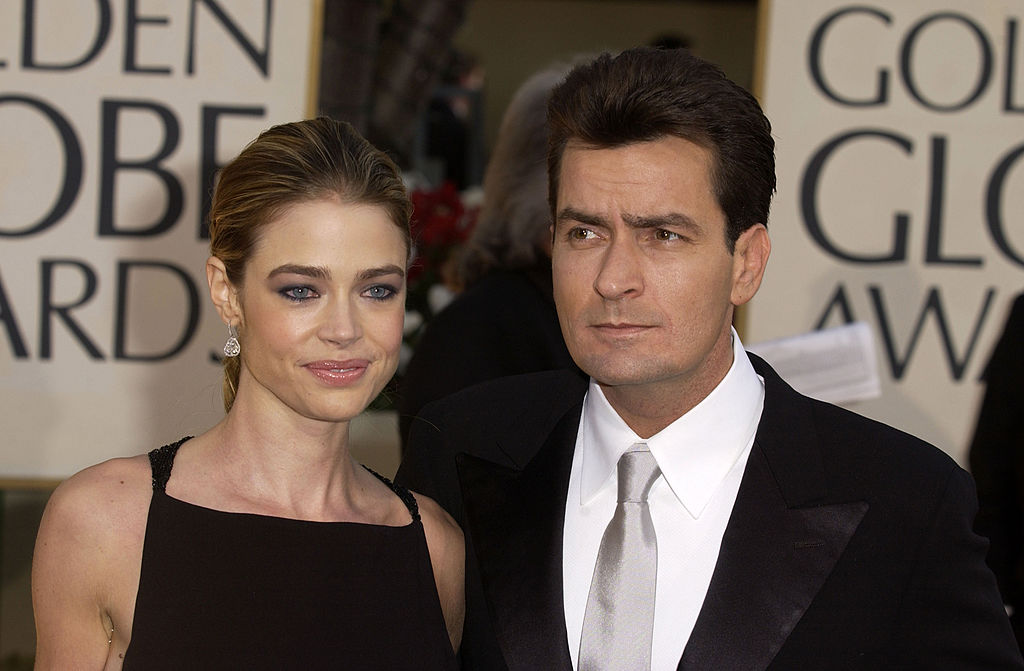 Denise Richards smiling, standing next to Charlie Sheen who is looking in the opposite direction