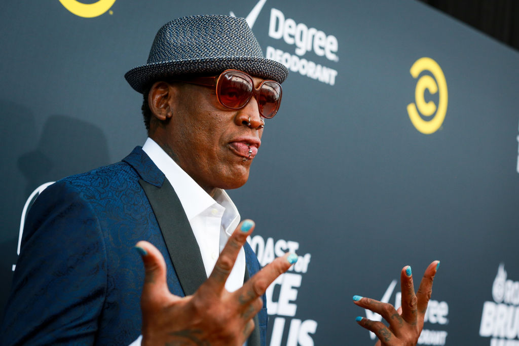 Dennis Rodman holding out his hands, smiling slightly in front of a repeating background