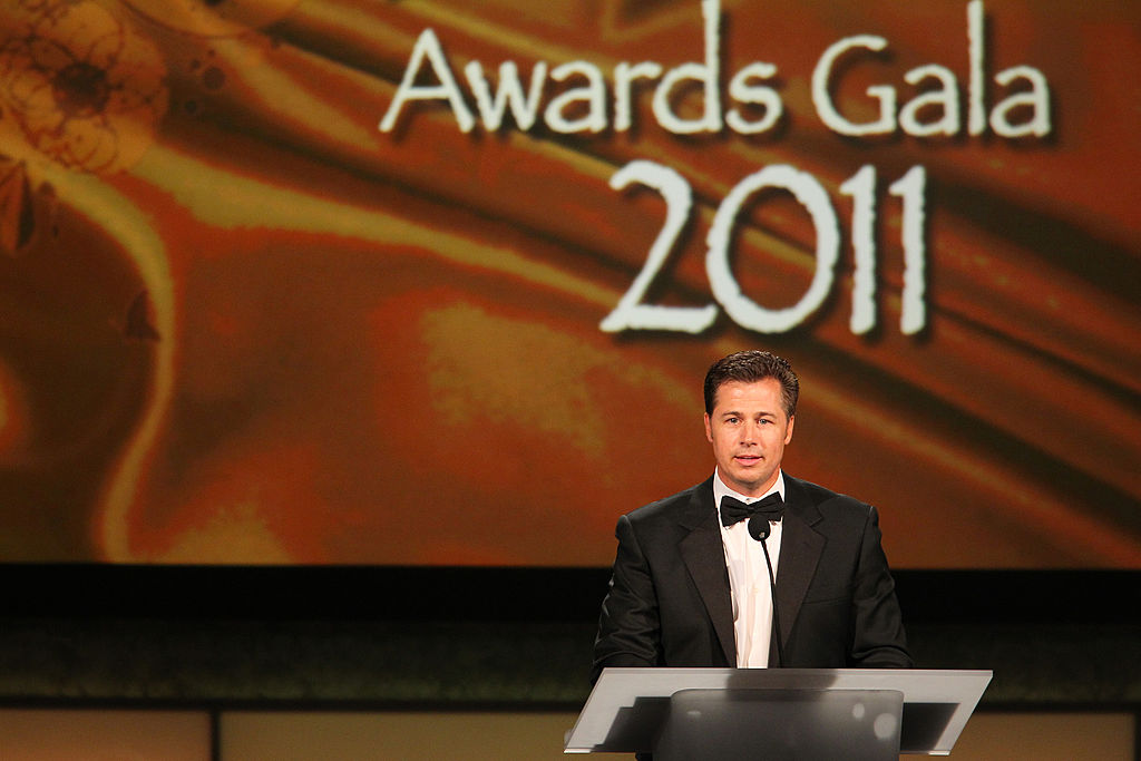 Doug Pitt smiling at a podium for a charity gala
