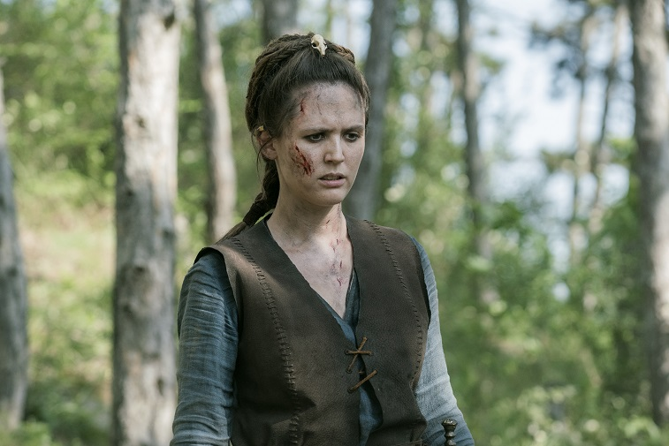 Emily Cox as Brida in 'The Last Kingdom' stands in the woods with blood on her face.