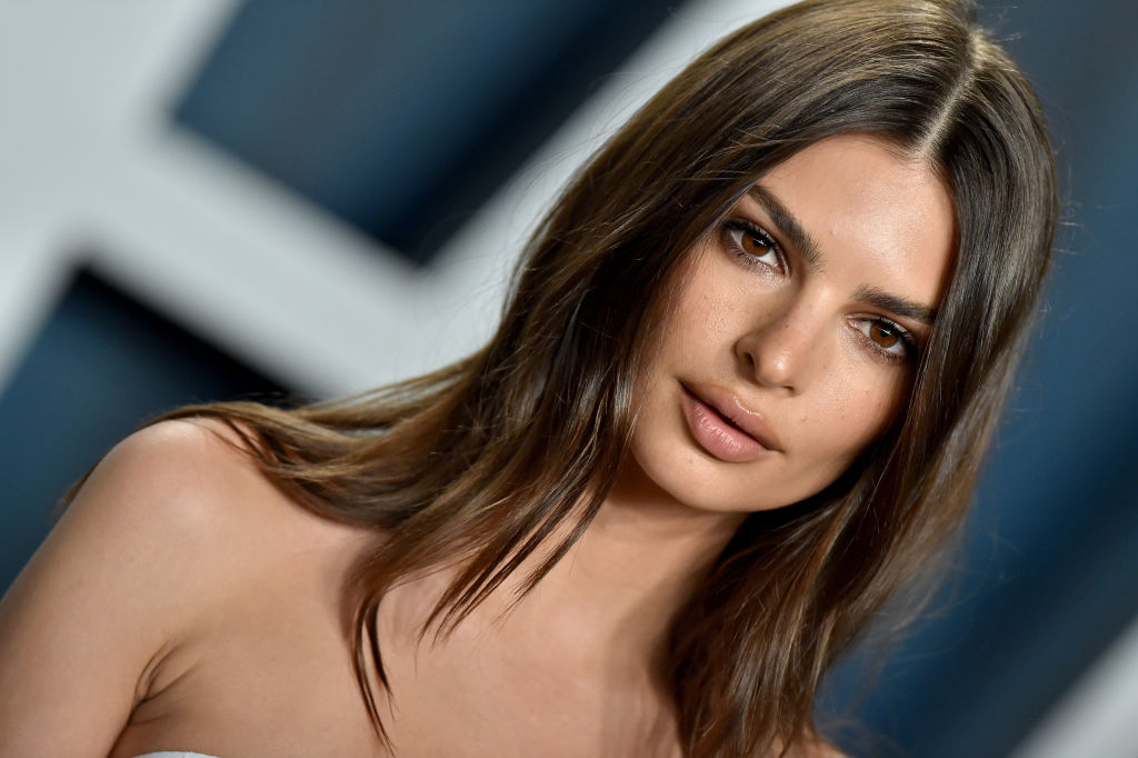Emily Ratajkowski not smiling with her hair down wearing a sleeveless dress