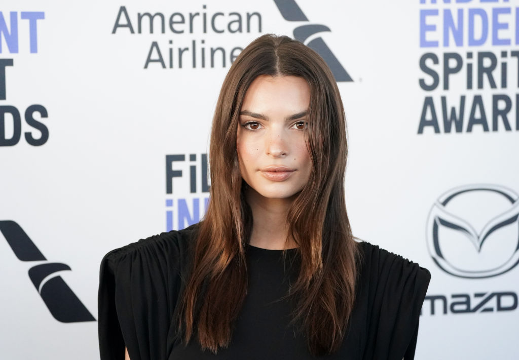 Emily Ratajkowski smiling in front of a repeating black and white background