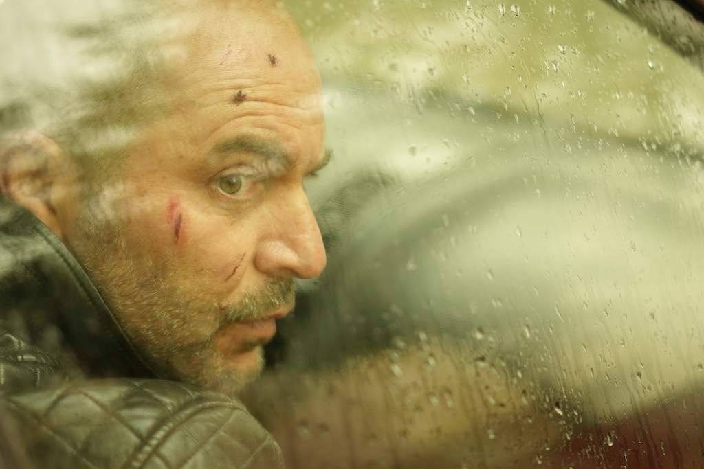 Production still with a sepia tone and a man with cuts on his face looking through a car window with rain on the glass