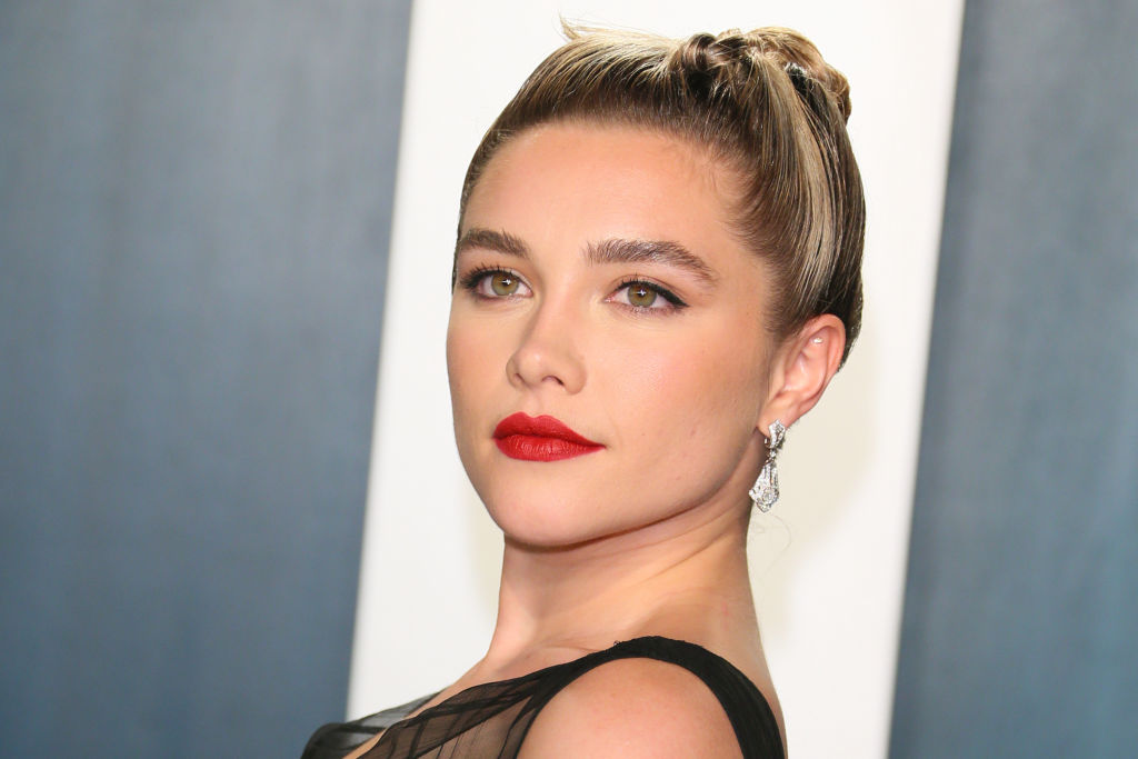 Florence Pugh slightly smiling in front of a blue and white background