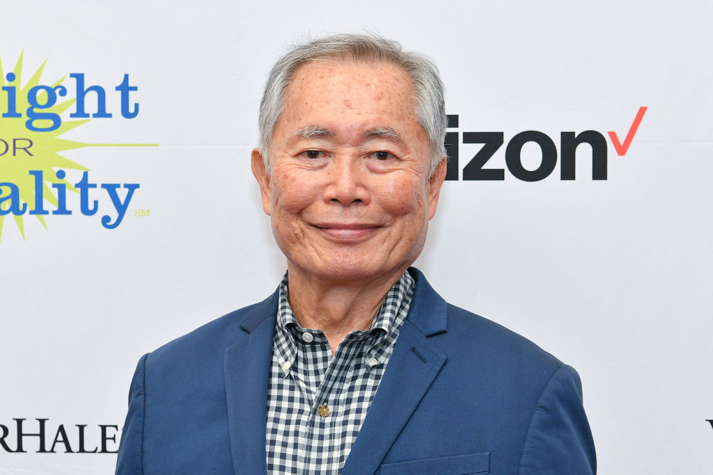 George Takei smiling in front of a repeating background