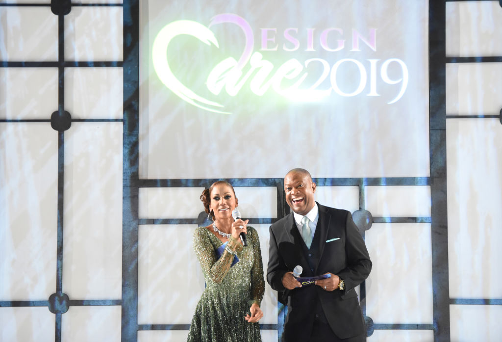 Holly Robinson Peete and Rodney Peete smiling and laughing on a stage