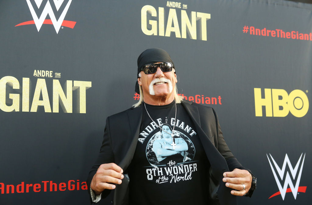 Hulk Hogan smiling in front of a black background with a repeating logo