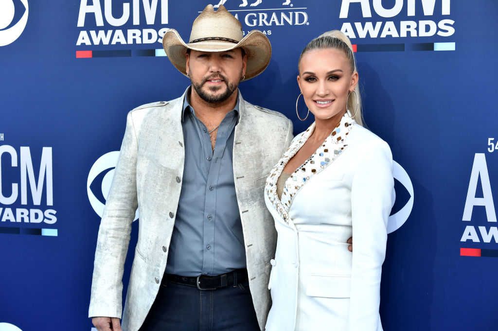 Jason and Brittany Aldean smiling at the camera in front of a blue backdrop with repeating logos