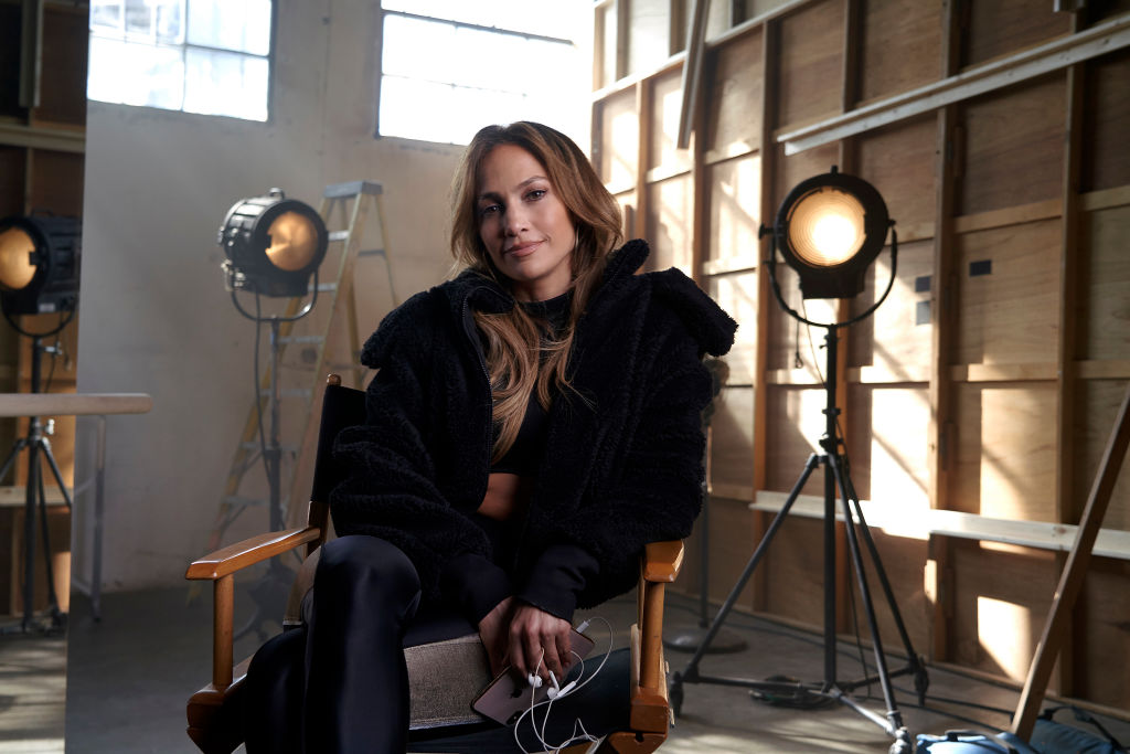 Jennifer Lopez sitting in a chair smiling at the camera wearing all black