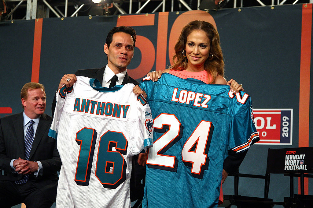 Jennifer Lopez and Marc Anthony holding up Miami Dolphins uniforms