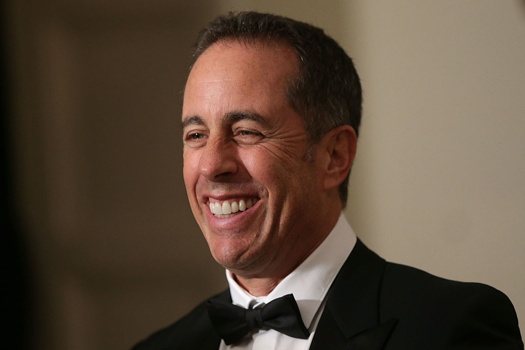 Jerry Seinfeld laughing in a tuxedo