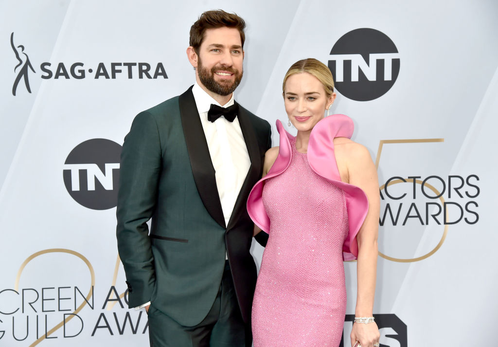 John Krasinski and Emily Blunt smiling in front of a white repeating background