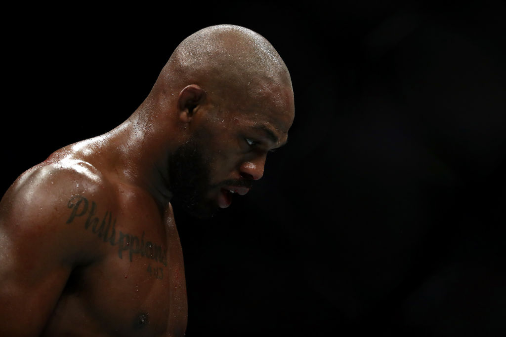 Jon Jones walks to his corner in between rounds against Dominick Reyes in their UFC Light Heavyweight Championship bout during UFC 247