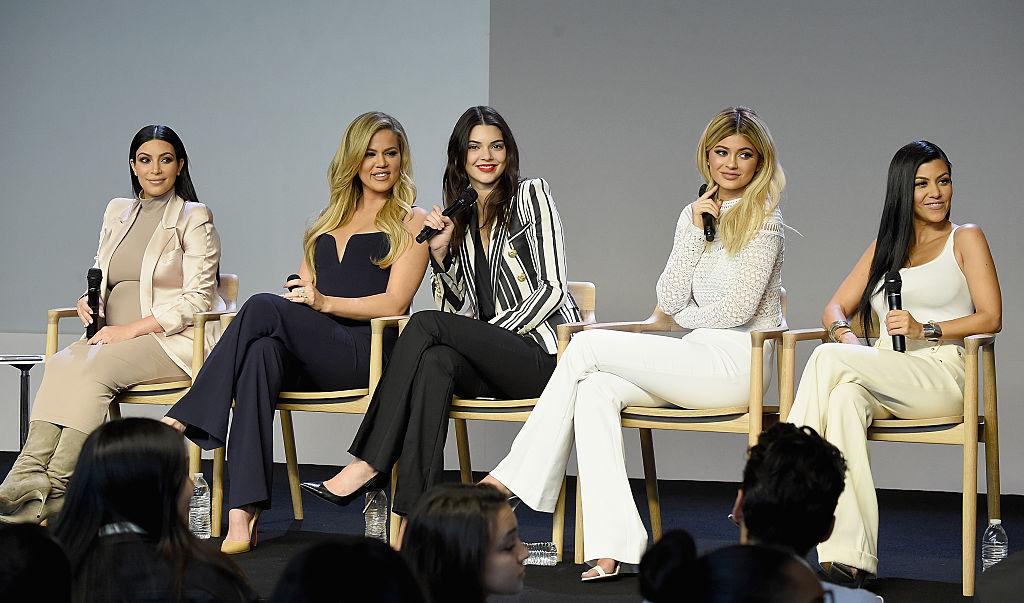 Kim Kardashian, Khloé Kardashian , Kendall Jenner, Kylie Jenner and Kourtney Kardashian on a stage holding microphones smiling