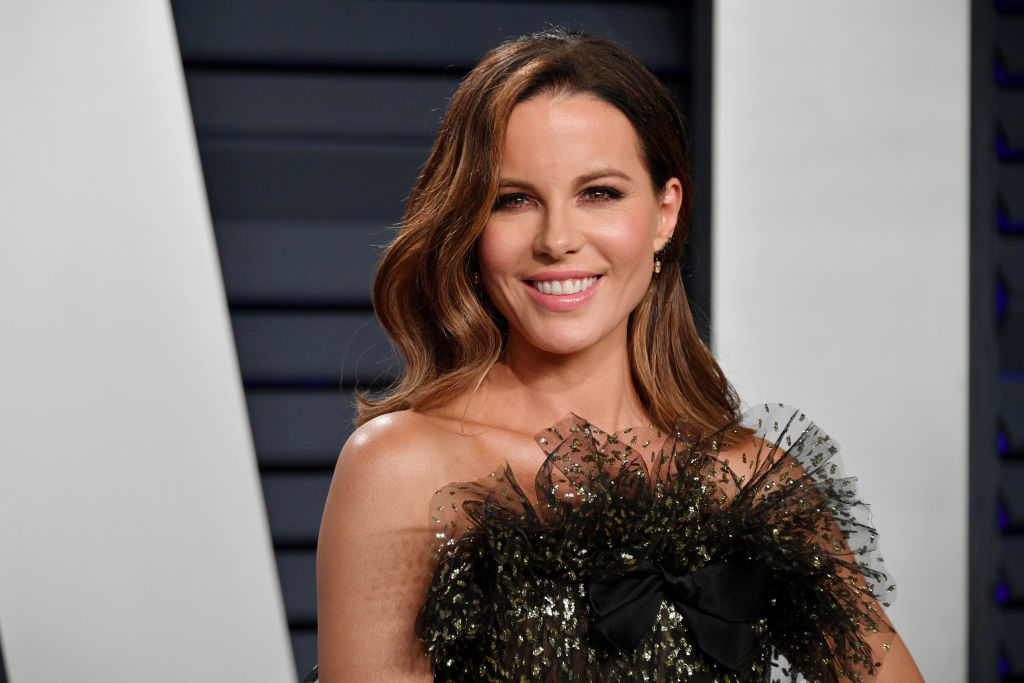 Kate Beckinsale smiling in a black and gold dress