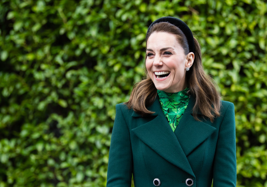 Kate Middleton laughing, wearing all green, in front of bushes