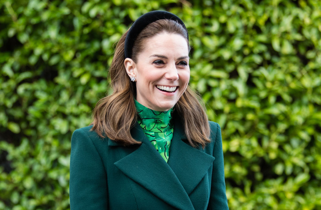 Kate Middleton smiling and looking off camera, wearing green in front of a green background