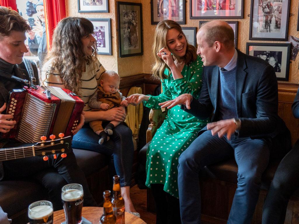 Prince William, Duke of Cambridge and Catherine, Duchess of Cambridge smiling in a pub