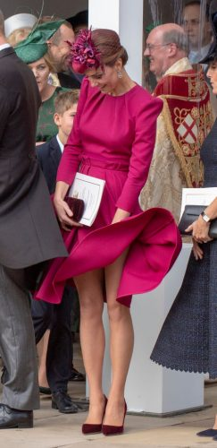 Kate Middleton keeps her dress from blowing in the wind