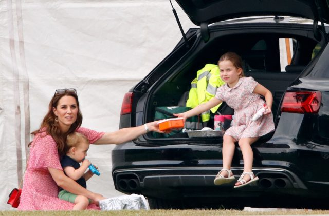 Kate Middleton sits with Prince Louis on her lap as she hands box to Princess Charlotte