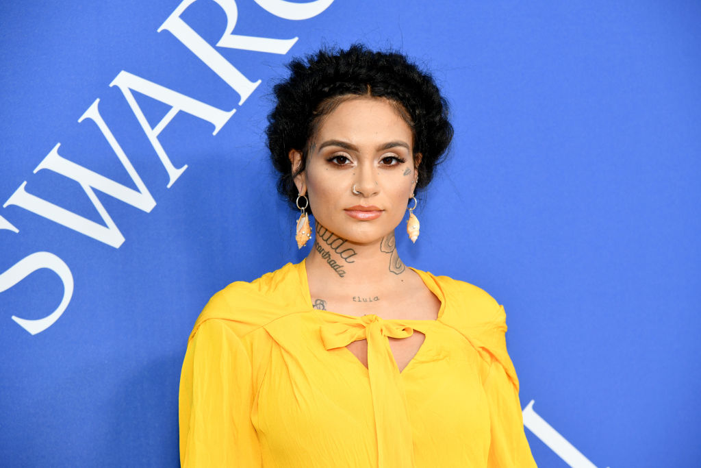 Kehlani smiling slightly wearing yellow in front of a blue background