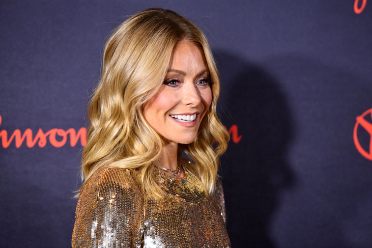 Kelly Ripa smiling in front of dark blue backdrop