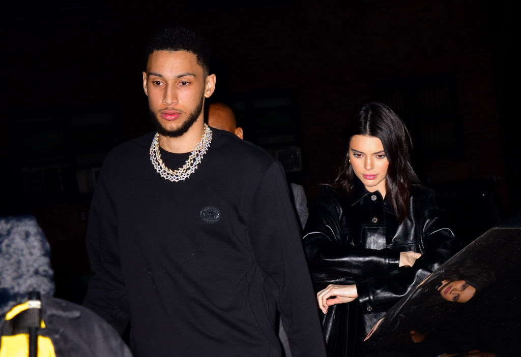 Ben Simmons looking off camera and Kendall Jenner slightly behind him looking down with arms crossed