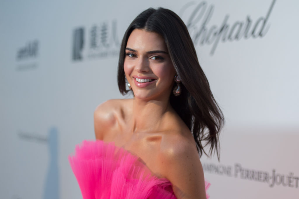 Kendall Jenner smiling over her shoulder in front of a repeating background