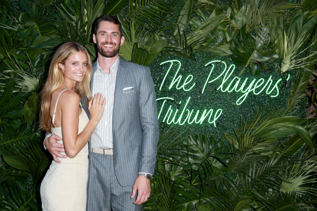 Kevin Love and Kate Bock smiling in front of a plant wall