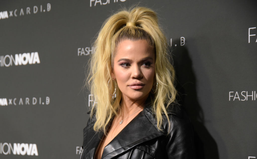 Khloé Kardashian looking off to the side in front of a gray background