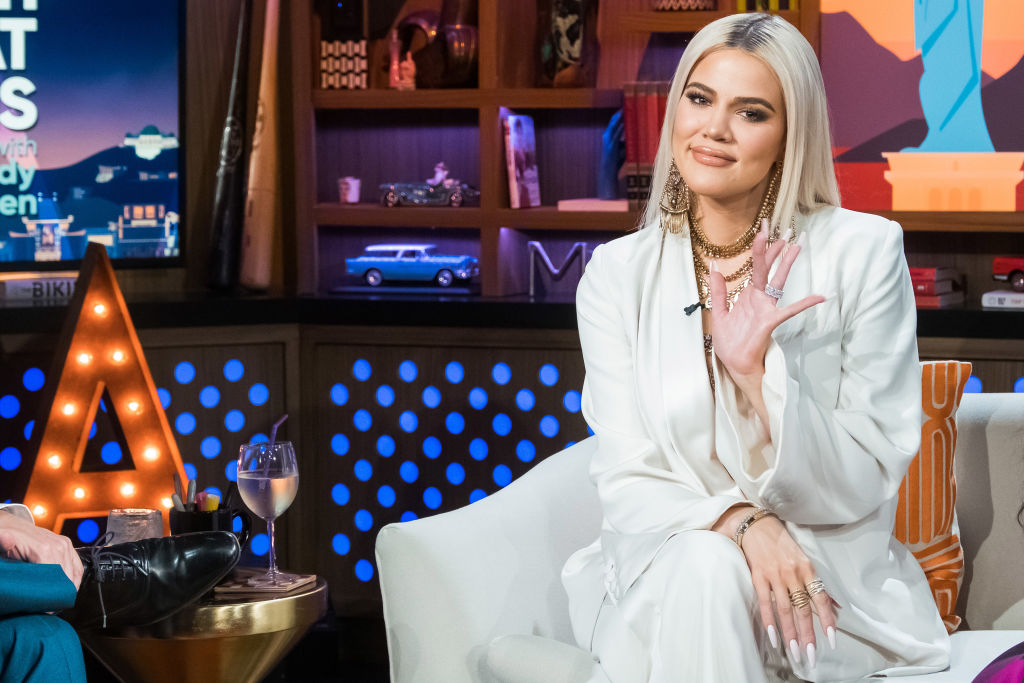 Khloé Kardashian smiling and waving while sitting on a couch