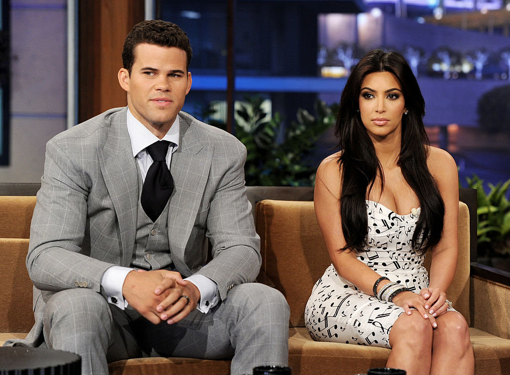 Kris Humphries and Kim Kardashian sitting on a couch, not smiling