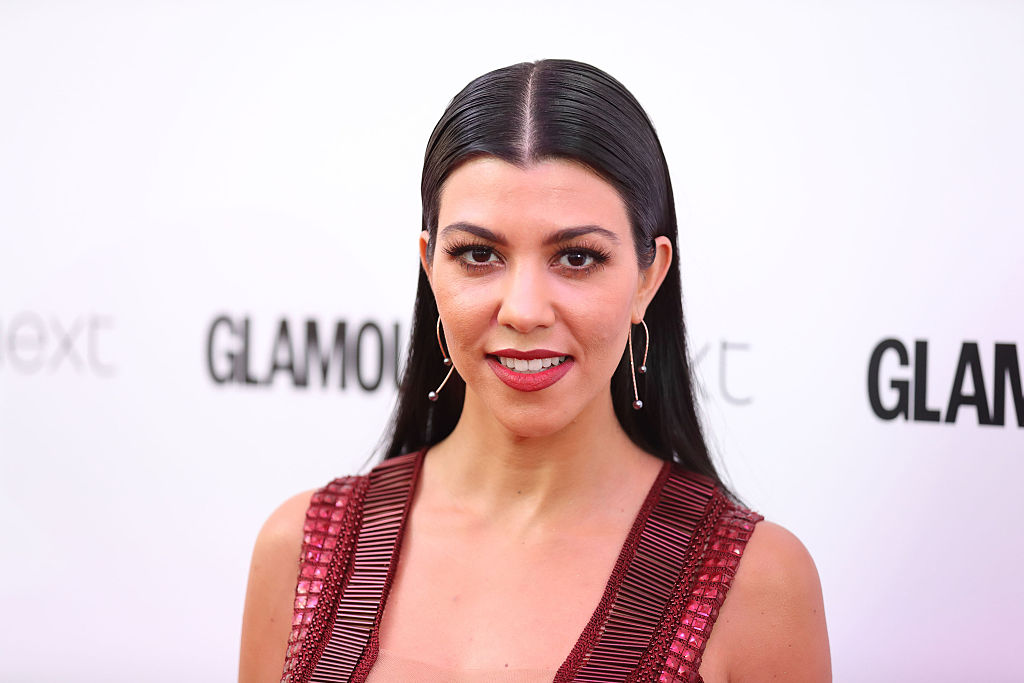 Kourtney Kardashian wearing red, smiling at the camera in front of a white background with repeating logos