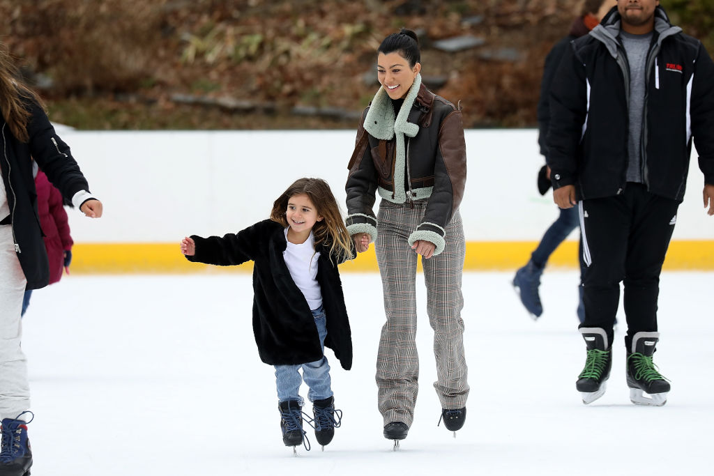 Kourtney Kardashian and Penelope Disick smiling while ice skating in central park