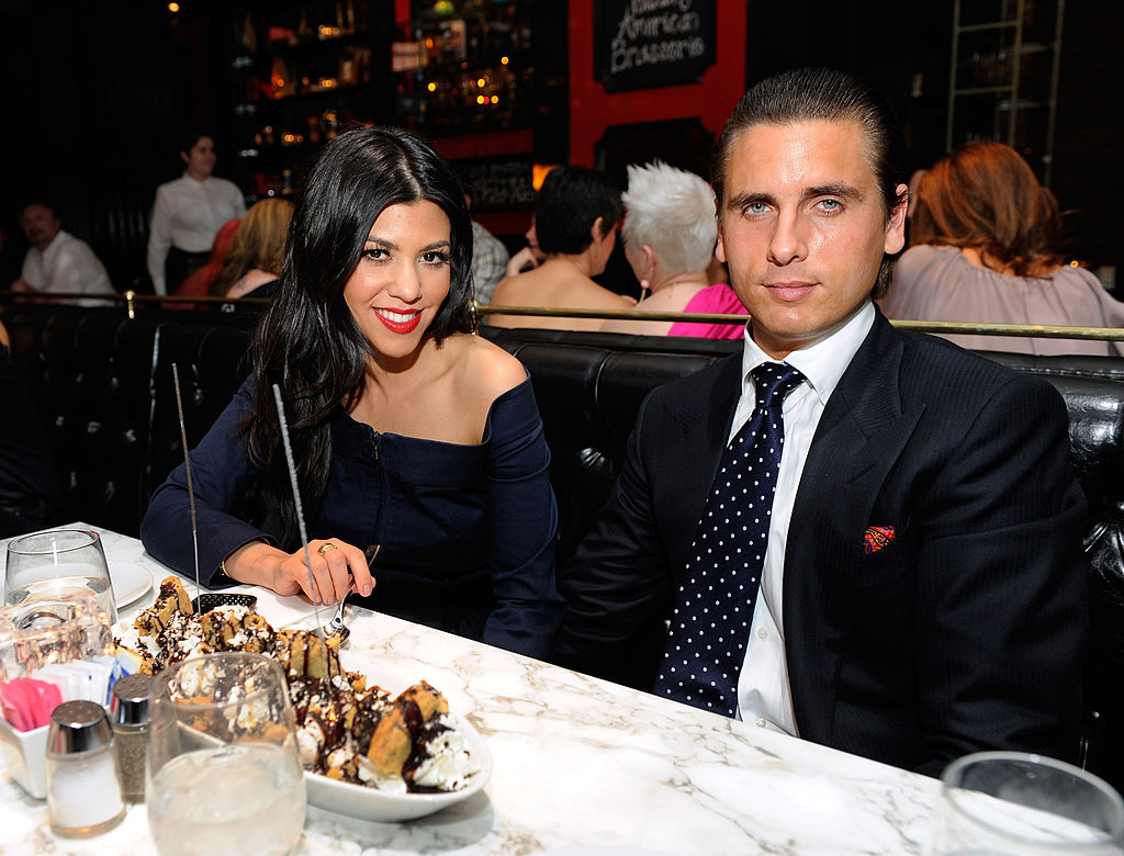 Kourtney Kardashian and Scott Disick smiling sitting at a table