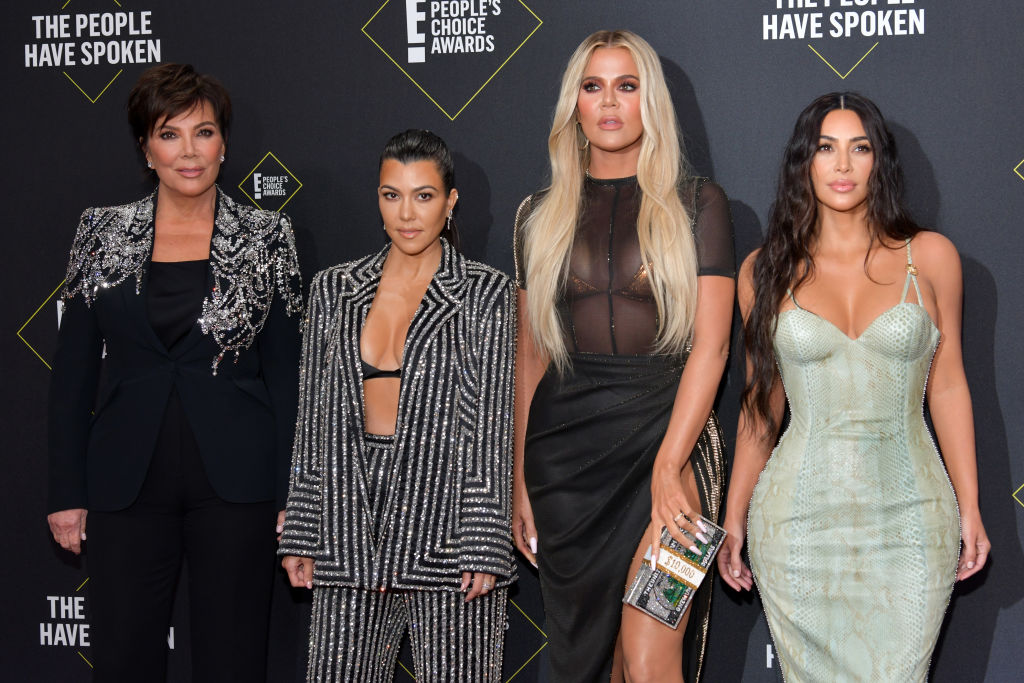Kris Jenner, Kourtney Kardashian, Khloé Kardashian and Kim Kardashian West smiling in front of a black background with repeating logo
