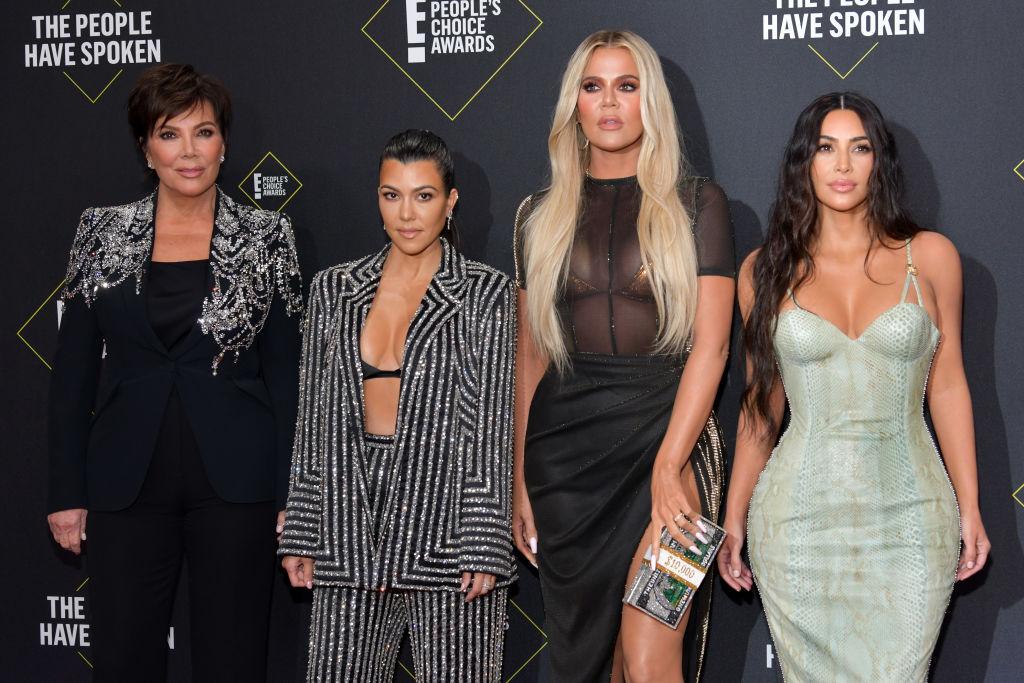Kris Jenner, Kourtney Kardashian, Khloé Kardashian and Kim Kardashian West smiling in front of a black background with repeating logo