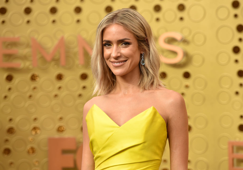 Kristin Cavallari smiling at the camera in front of a gold background wearing a yellow dress