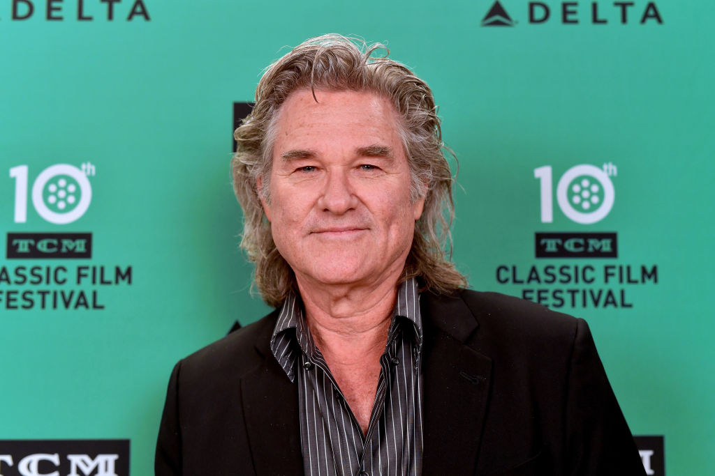 Kurt Russell smiling in front of a repeating background