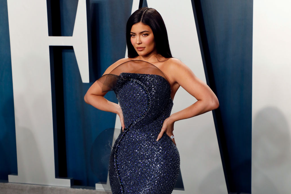 Kylie Jenner slightly smiling wearing a glittery blue dress with her hands on her hips