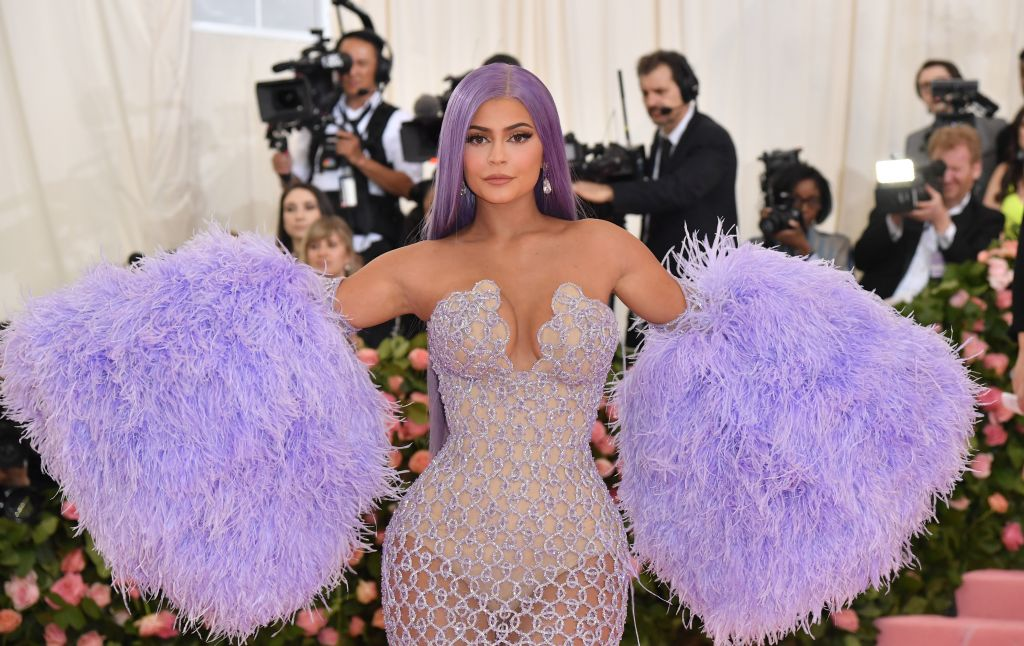 Kylie Jenner smiling slightly in a purple dress with giant fluffy arm gloves