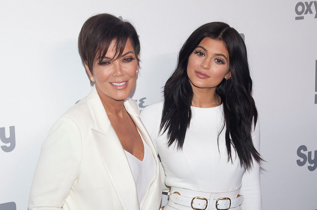 Kris Jenner and Kylie Jenner smiling wearing white in front of a white backdrop