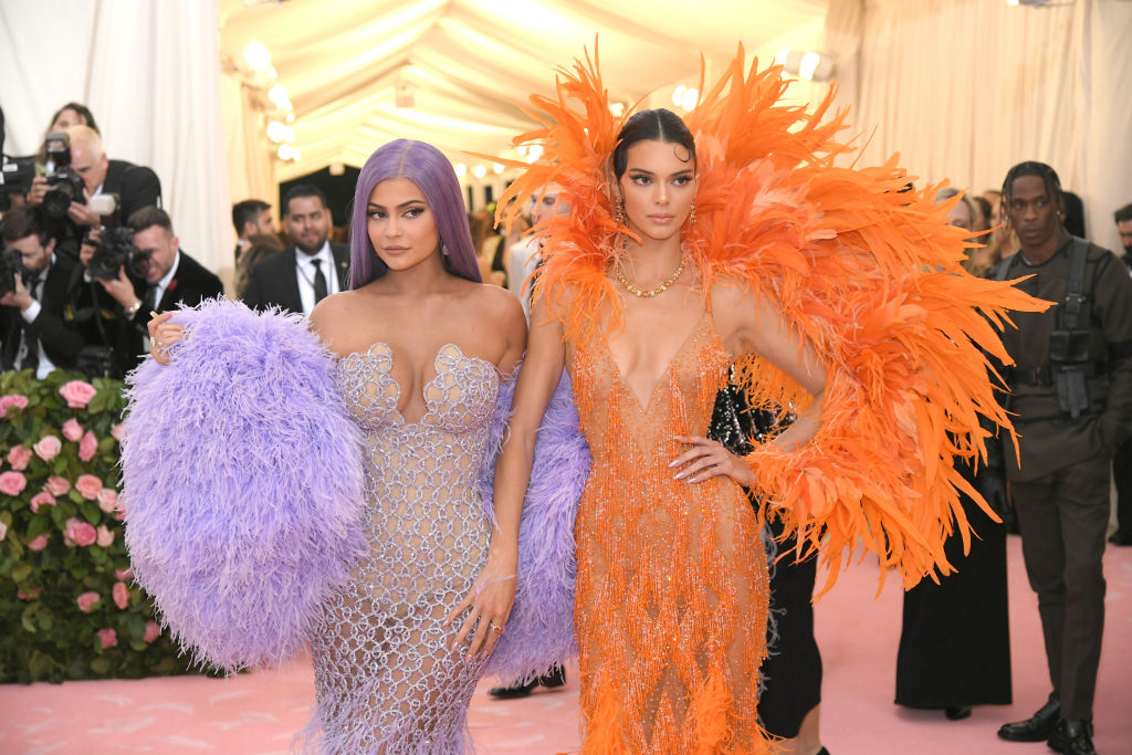 Kylie Jenner and Kendall Jenner in purple and orange looking to the side
