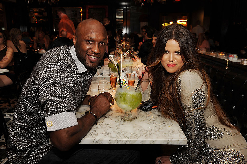 Lamar Odom and Khloé Kardashian sitting on opposite sides of a dinner table, smiling at the camera